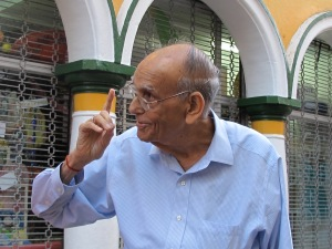 "Doulatram Boolchand Nandwani (affectionately ""Dada"") will be turning 91 this year and still works from 10-1 pm every day [pictured pointing to Boolchand's in Punda]"