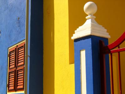 """All of the primary colors – red, yellow, and blue – are present on this boldly painted gate before a beautifully restored house on one of the Caribbean's most prosperous islands. The light is as bold as the color – the interplay of light and shadow enriches the color with a three dimensional effect. The perfect condition of these sleek colors tell us that whoever lives here appreciates beauty and has the means to maintain it. All of which provides a good metaphor for Willemstad itself."" Source: www.pbase.com."