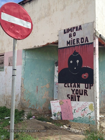 """Leslie writes: """"Even Curacao's public service announcements have an artistic twist. I came across this anti-littering sign in a residential neighborhood east of Willemstad. In English and Papiamentu it bears the message, """"Clean up your sh@#"""""""