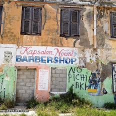 "Leslie writes: ""The buildings throughout Curacao are beautiful – even when they are crumbling. Many commercial buildings are covered with painted advertisements for beauty salons, supermarkets and restaurants. This [roving] barber shop was tagged with the words ""no pichi aki"" in Papiamentu-Dominican-Spanish (""don't piss here"", in English)"""