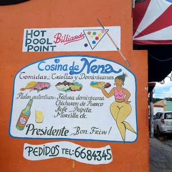 "Leslie writes: ""This ad for Nena's Dominican restaurant in Willemstad caught my eye. They are clearly targeting diners who like their women with curves!"" Also please note that they serve Presidente 'Bon Friw!' (Papiamentu)"